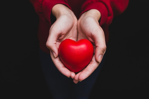 Hands holding a heart on a dark background Premium Photo