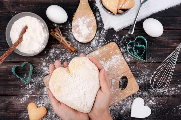 Hands holding heart-shaped dough Free Photo