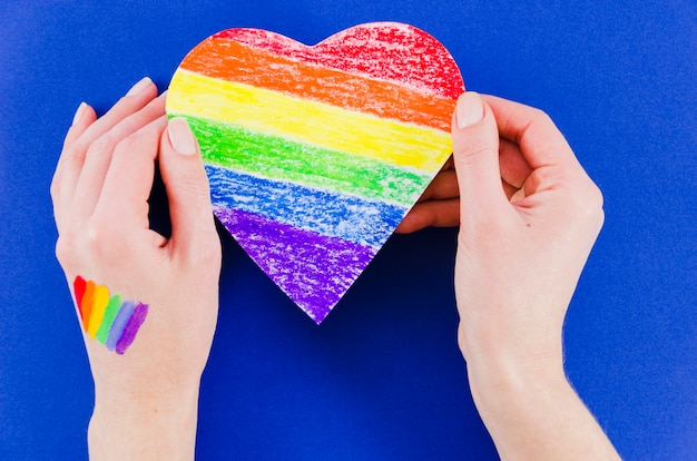 Hands holding a heart with pride day flag colors Free Photo
