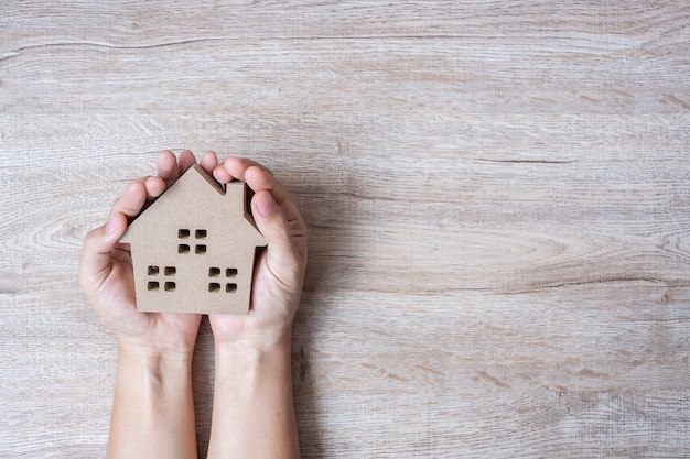 Hands holding house model on wood table background with copy space. Premium Photo