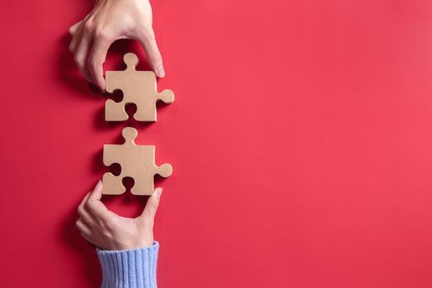 Hands holding jigsaw. concept for teamwork building a success. Premium Photo