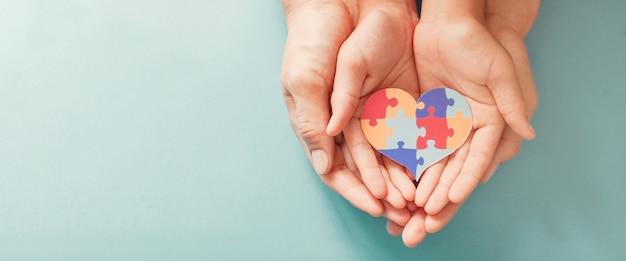직소 퍼즐 심장 모양, 세계 자폐증 인식의 날을 들고 손 프리미엄 사진