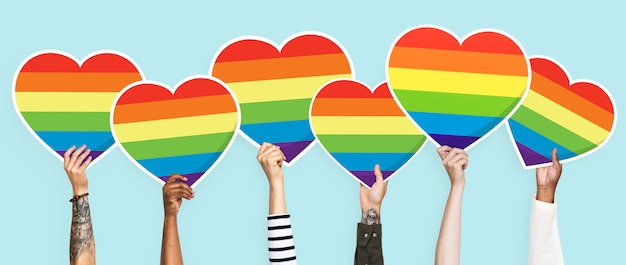 Hands holding a lgbt rainbow heart graphic Premium Photo