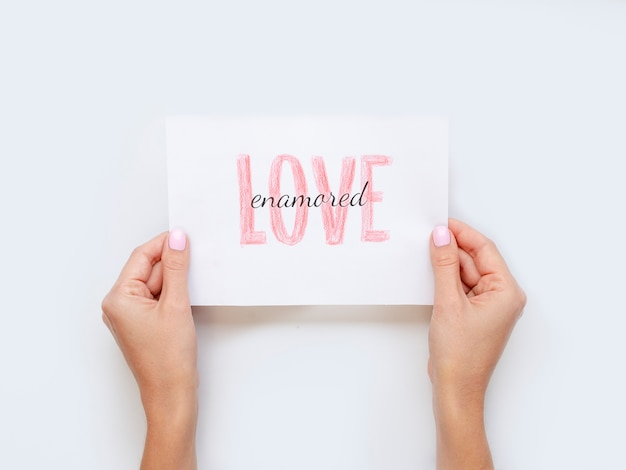 Hands holding love paper flat lay Free Photo