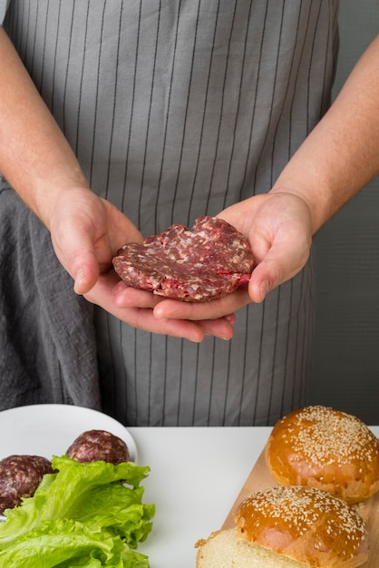 Hands holding meat for burger Free Photo