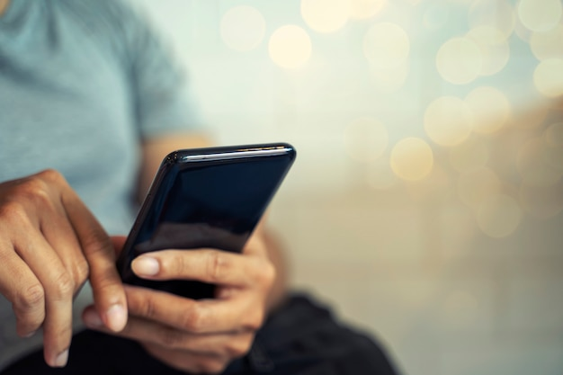 両手携帯電話の背景をぼかした写真を携帯電話。技術とビジネスのコンセプトです。 Premium写真
