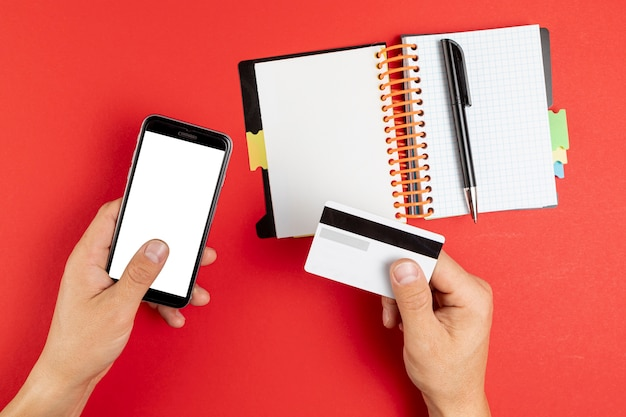 Hands holding a notebook and phone mock up Free Photo