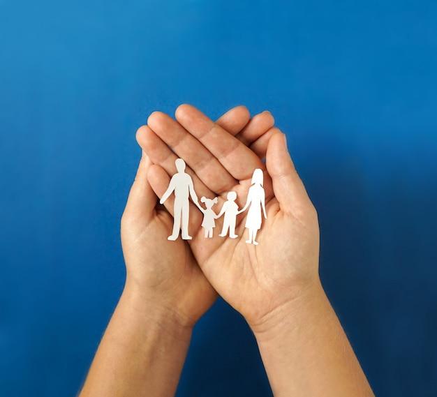 Руки держат бумаги семьи вырез, концепция социального дистанцирования, covid19 на синем фоне цвета, защита семьи Premium Фотографии
