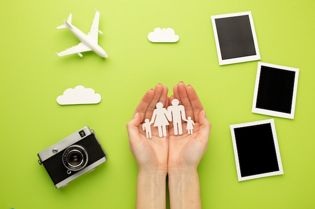 Hands holding paper family next to instant photos Free Photo