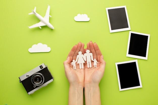 Руки держат бумажную семью рядом с мгновенными фотографиями Premium Фотографии