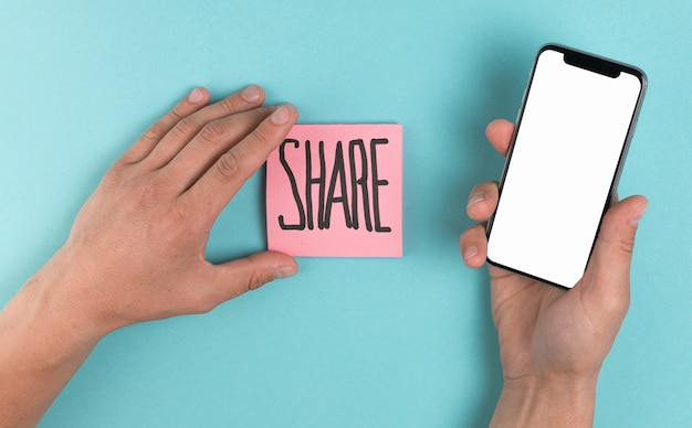 Hands holding a phone mock up and sticky notes Premium Photo