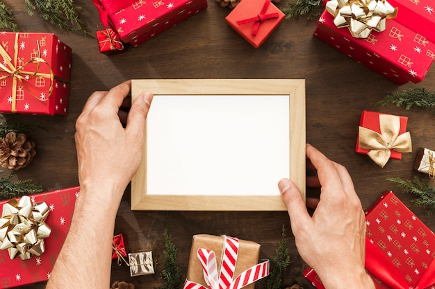 Hands holding photo frame between gift boxes Free Photo
