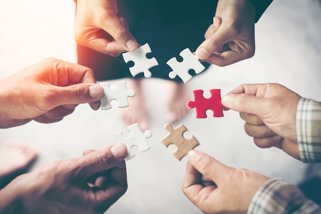 Hands holding piece of blank jigsaw puzzle for teamwork workplace success and strategy concept. Premium Photo