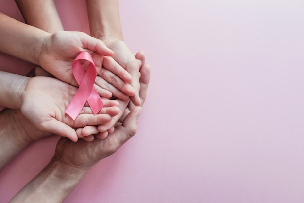 Hands holding pink ribbons, breast cancer awareness and october pink day 5787514