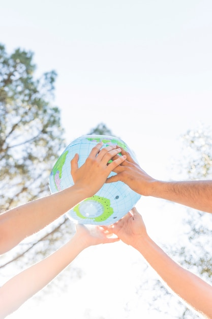 Hands holding planet model in nature Free Photo