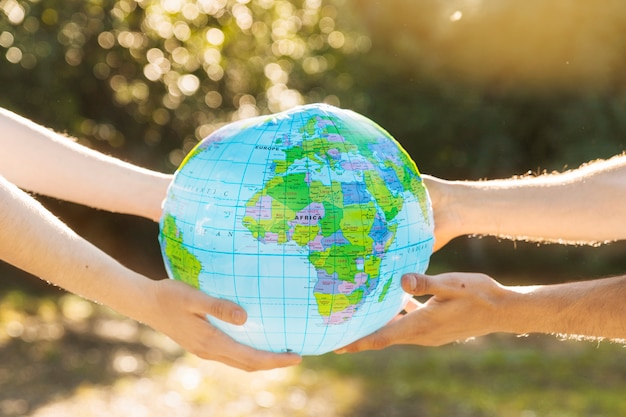 Hands holding planet model in sunlight Free Photo