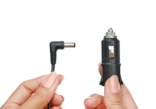 Hands holding plug socket in car 12 volt to charging for etc. isolated on white background Premium Photo
