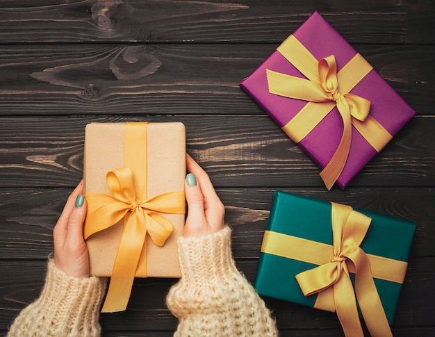 Hands holding present for christmas on wooden background Free Photo