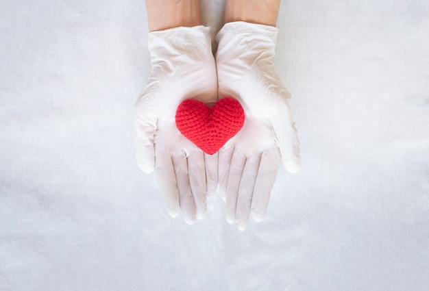 赤いハートを持っている手。心臓の健康、心臓病学、医者の日、世界の心臓の日。高血圧。 Premium写真