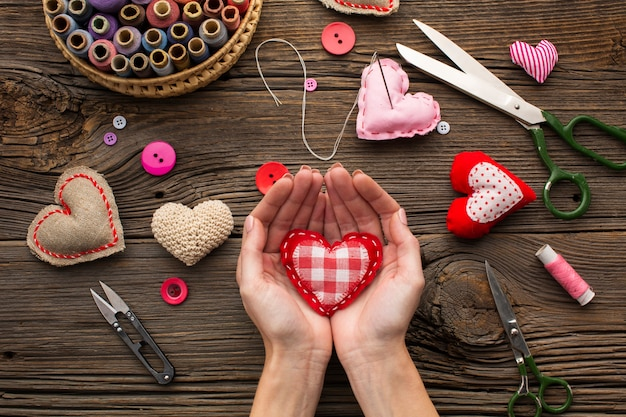 Hands holding a red heart shape on wooden background Free Photo