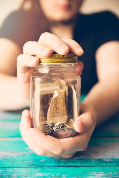 Hands holding savings jar Free Photo