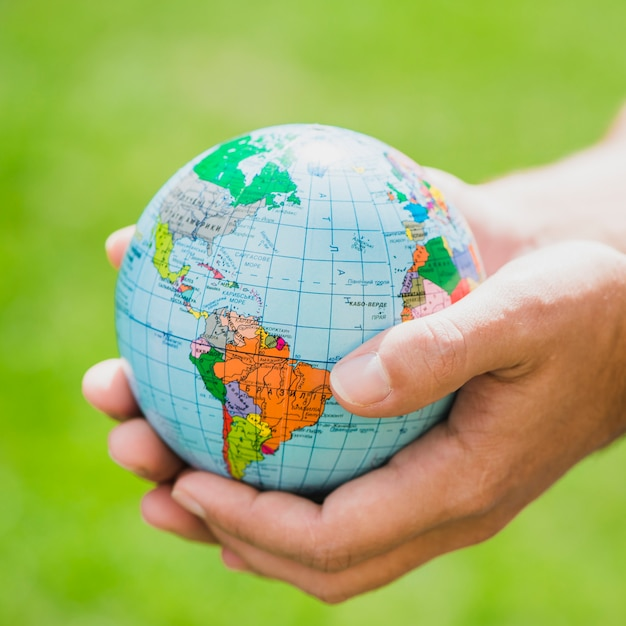 Hands holding small globe against green background Free Photo