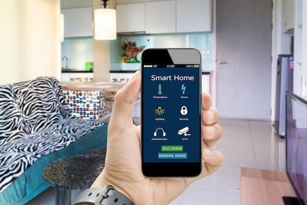 흐리게 침대 방에 앱 스마트 홈 스마트 폰을 손에 들고 프리미엄 사진