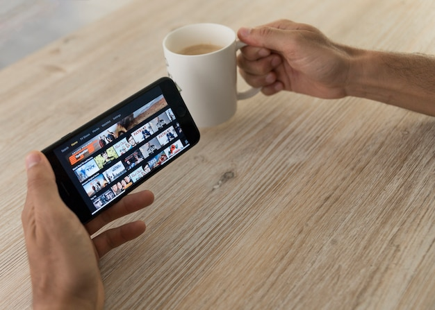 Hands holding smartphone showing amazon prime video app Free Photo
