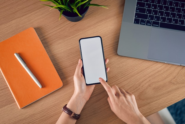 Hands holding smartphone with blank screen, laptop with book and accessories on wood table. Premium Photo