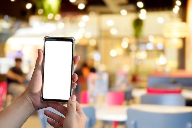 Hands holding smartphone with empty screen Premium Photo
