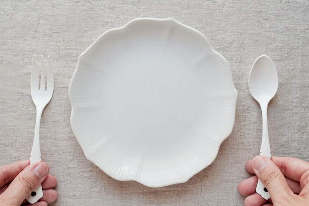 Hands holding spoon and fork with empty plate Premium Photo