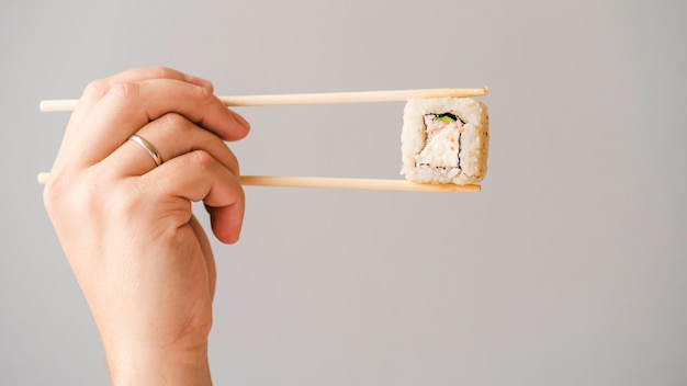 Hands holding sushi roll with chopsticks Free Photo