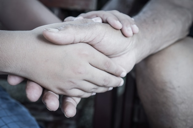 Hands holding together take care of asian teenage touching elderly Premium Photo