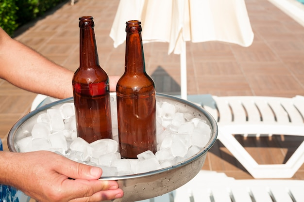 Hands holding a tray filled with ice cubes and beer Free Photo