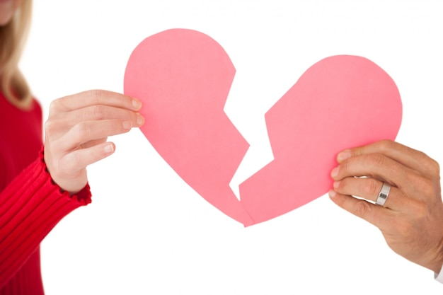 Hands holding two halves of broken heart Premium Photo