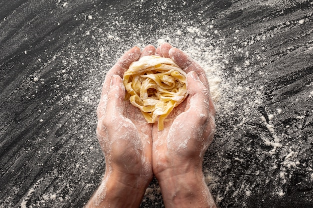 Hands holding uncooked tagliatelle Free Photo