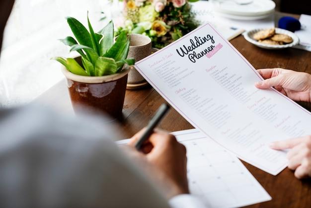 Mani che tengono la preparazione di informazioni della lista di controllo del pianificatore di nozze Foto Gratuite