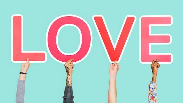 Mani che tengono la parola amore Foto Gratuite