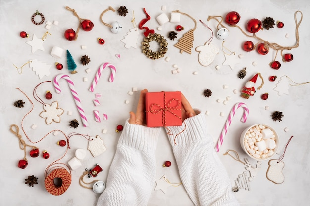 Hands holding wrapped gift box. christmas decoration with gift boxes, rope, marshmallows, gingerbread cookies Premium Photo