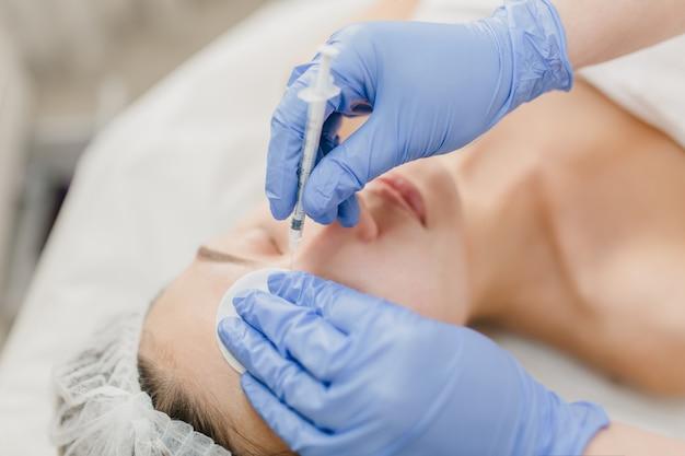 Руки в голубых свечениях косметолога на работе с красивой женщиной во время инъекции на лице. омоложение, профессиональное, здравоохранение, медицина, лечебная терапия, уход за кожей, ботокс Бесплатные Фотографии