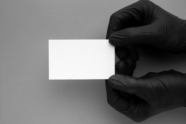 Руки в перчатках, держа визитную карточку Бесплатные Фотографии