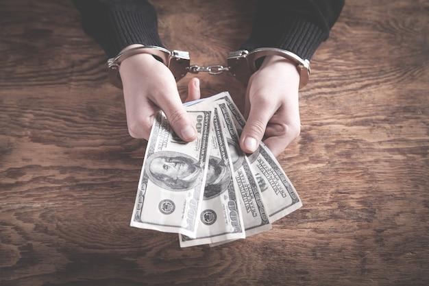 ドル紙幣を持っている手錠の手。腐敗 Premium写真