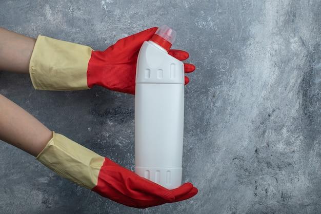 청소 용품을 들고 보호 장갑에 손을 댄다. 무료 사진