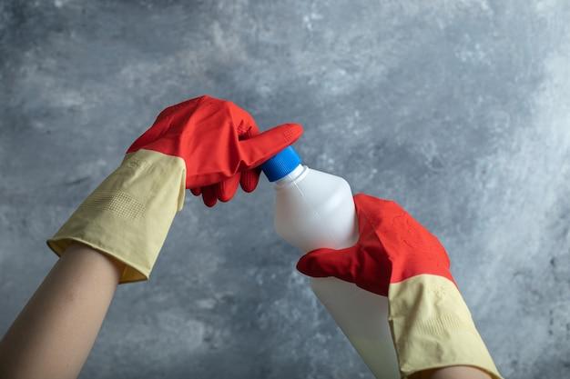표백제의 용기를 여는 빨간 장갑에 손을. 무료 사진