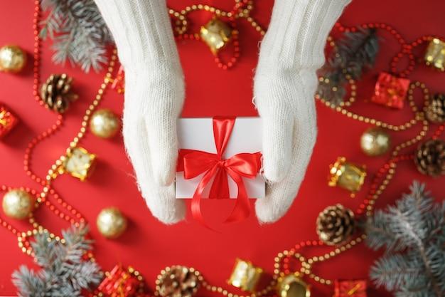 赤い背景に贈り物を保持している白いニットミトンの手。赤いリボンの白い箱。持続可能な休日のライフスタイル。クリスマスの飾り Premium写真