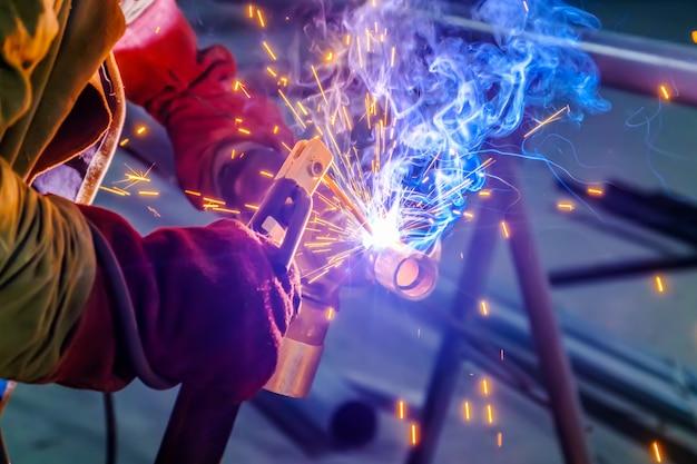 Hands of industrial worker with protective gloves welding metal steel part Premium Photo