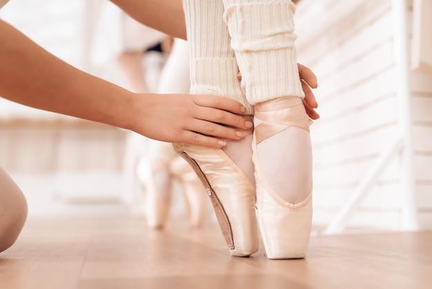Hands of kid legs of ballerina in pointe shoes. Premium Photo