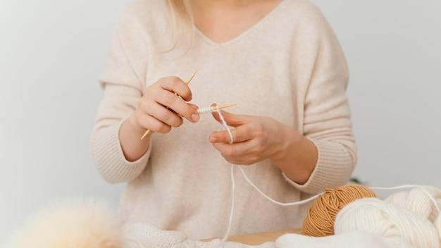 Mani che lavorano a maglia con il primo piano del filo bianco Foto Gratuite