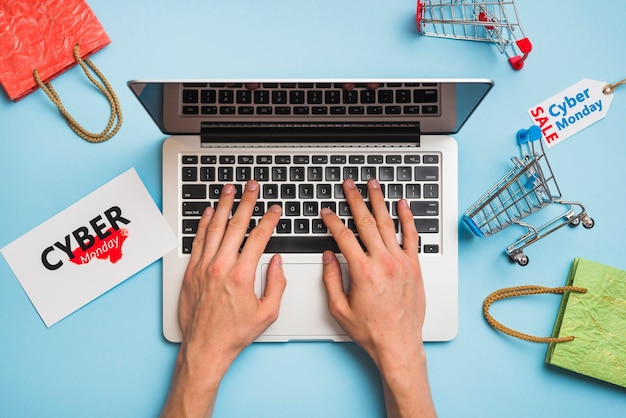 Hands on laptop near tags with cyber monday title Free Photo