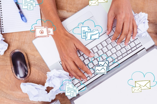Hands on laptop with icons Free Photo